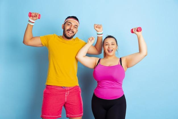 파란색 배경에 밝은 옷 훈련에 젊은 꽤 백인 부부 스포츠, 인간의 감정, 표현, 건강한 라이프 스타일, 관계, 가족의 개념. 무게로 훈련하고 재미있게 보내십시오. 무료 사진