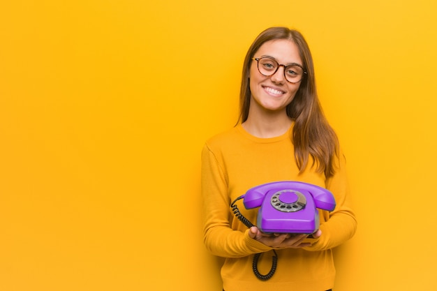 Young pretty caucasian woman cheerful with a big smile. she is holding a vintage telephone. Premium Photo