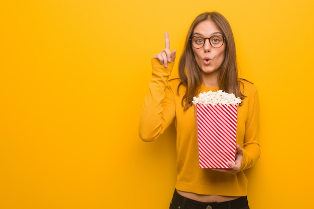 Young pretty caucasian woman having a great idea, concept of creativity. she is eating popcorns. Premium Photo