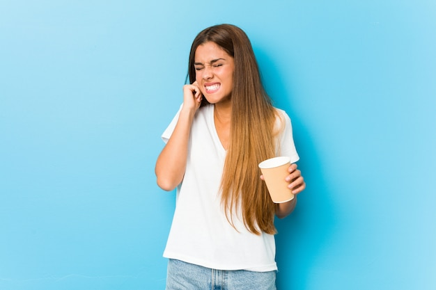 Young pretty caucasian woman holding a takeaway coffee covering ears with hands. Premium Photo