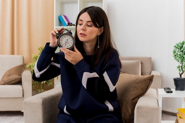 설계 된 거실에서 안락의 자에 앉아 알람 시계를 찾고 젊은 꽤 백인 여자 무료 사진