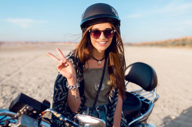 Молодая довольно жизнерадостная женщина, сидящая на мотоцикле на пляже и демонстрирующая вывески, одетая в стильный кроп-топ, рубашки, прекрасно облегает стройное прирученное тело и длинные волосы. открытый образ жизни портрет. Бесплатные Фотографии