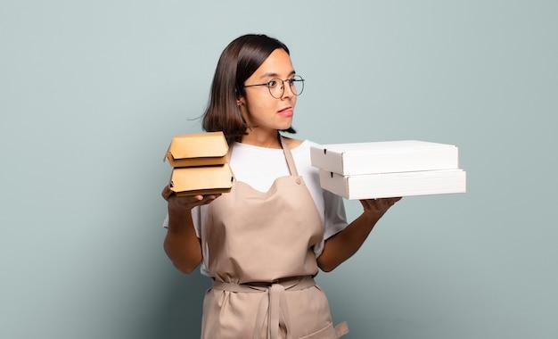 Молодая красивая женщина шеф-повара. концепция быстрого питания Premium Фотографии