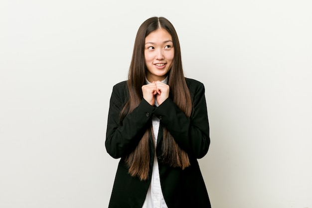 Young pretty chinese business woman keeps hands under chin, is looking happily aside. Premium Photo