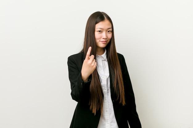 若いかなり中国のビジネス女性があなたに指を指して、まるで招待が近づくように。 Premium写真
