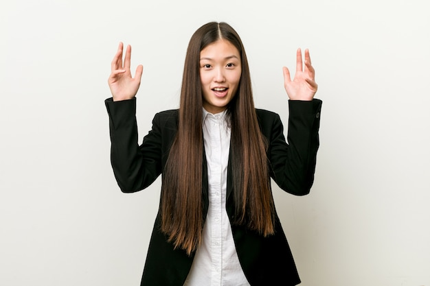 Young pretty chinese business woman receiving a pleasant surprise, excited and raising hands. Premium Photo