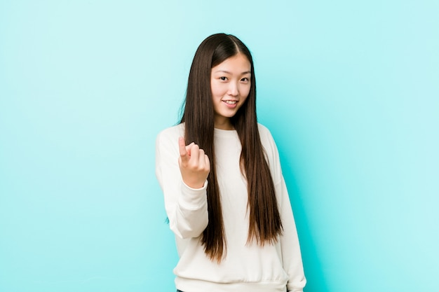 Young pretty chinese woman pointing with finger at you as if inviting come closer. Premium Photo