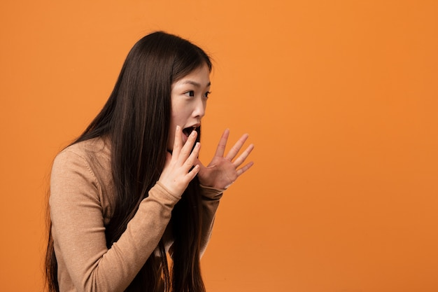 Young pretty chinese woman shouts loud, keeps eyes opened and hands tense. Premium Photo