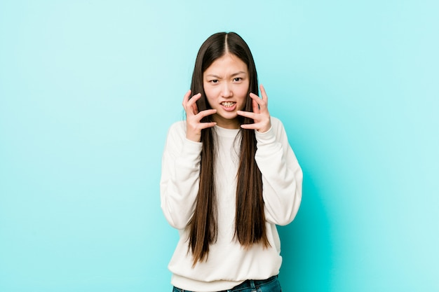 Young pretty chinese woman upset screaming with tense hands. Premium Photo