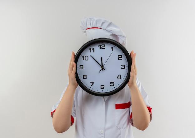 Giovane cuoco grazioso in uniforme del cuoco unico che tiene l'orologio e che si nasconde dietro esso Foto Gratuite