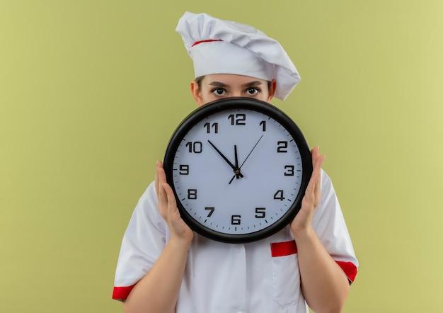 Piuttosto giovane cuoco in uniforme da chef holding e nascondersi dietro l'orologio isolato su sfondo verde Foto Gratuite