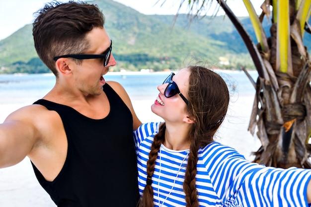 Giovane bella coppia di giovani viaggiatori che si divertono e fanno selfie in vacanza tropicale Foto Gratuite