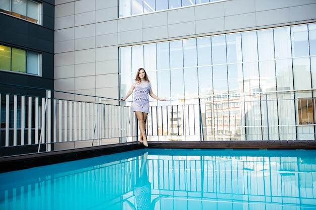 Молодая красивая модная спортивная женщина позирует на открытом воздухе летом в жаркую погоду в бикини в бассейне Бесплатные Фотографии