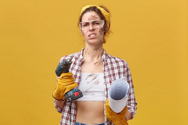 Giovane bella lavoratrice che indossa occhiali protettivi, guanti e camicia casual che tiene trapano e cianografia con uno sguardo disgustoso che aggrotta la fronte con riluttanza a riparare la sua stanza Foto Gratuite