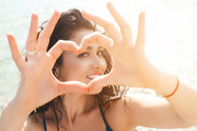 Young pretty girl on the beach making a heart with her hands into the camera. beautiful girl on summer time Premium Photo