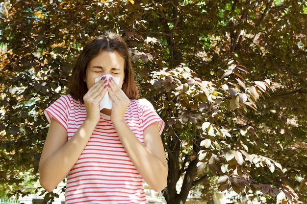 Young pretty girl blowing nose in front of tree. spring allergy concept Premium Photo