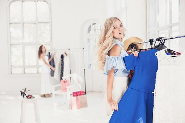 La giovane ragazza graziosa che sceglie e prova i vestiti al negozio Foto Gratuite