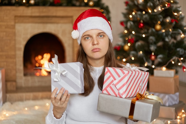 젊은 예쁜 여자는 그녀의 선물에 만족하지 않고 벽난로 근처에 포즈를 취하고 손에 선물 상자가있는 크리스마스 트리 프리미엄 사진