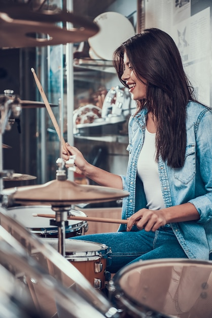 Young pretty girl is playing on drum kit in music store Premium Photo