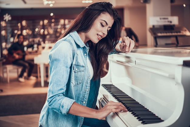 Young pretty girl is playing piano in music store. Premium Photo