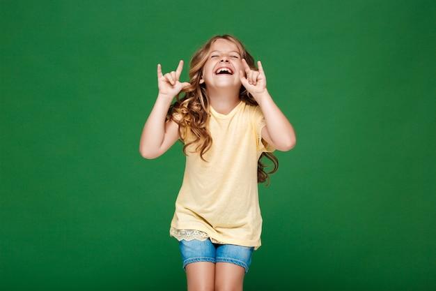Молодая красивая девушка смеется над зеленой стеной Бесплатные Фотографии