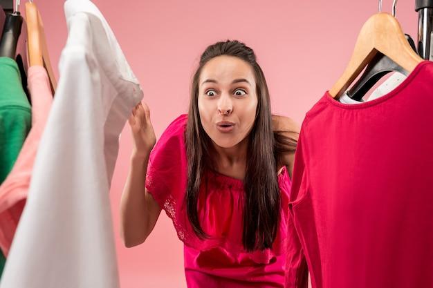 La giovane ragazza carina guarda i vestiti e prova mentre sceglie al negozio Foto Gratuite