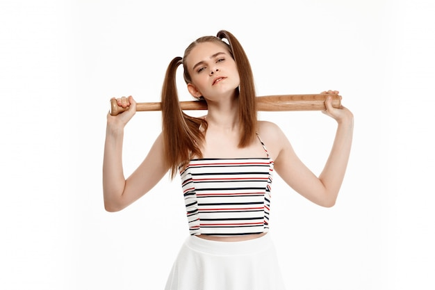 Young pretty girl posing with bat, isolated on white wall Free Photo