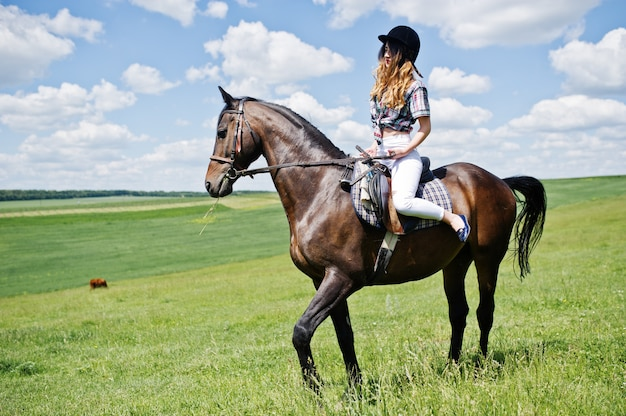 Young pretty girl riding a horse on a field at sunny day. Premium Photo