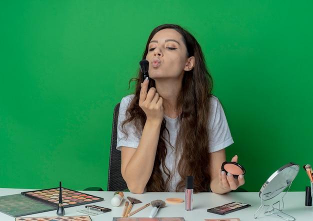 緑の背景に分離された赤面ブラシと赤面ブラシを見て、キスを身振りで示す化粧ツールで化粧テーブルに座っている若いかわいい女の子 無料写真