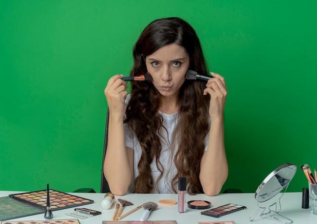 パウダーとチークのブラシを保持し、それらで頬に触れ、緑の背景に分離されたカメラを見て化粧ツールで化粧テーブルに座っている若いかわいい女の子 無料写真