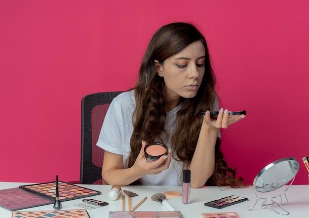 真っ赤な背景に分離されたパウダーを見てパウダーと赤面を保持している化粧ツールで化粧テーブルに座っている若いかわいい女の子 無料写真