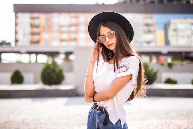 Young pretty girl with black hat and sunglasses outdoors on the sunny street Free Photo