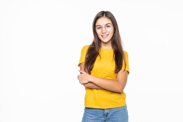 Молодая красивая девушка со скрещенными руками, изолированные на белой стене Бесплатные Фотографии