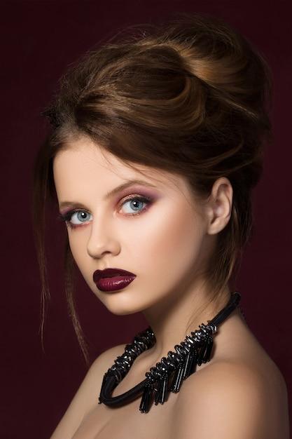 濃い赤の口紅と黒いネックレスのポーズの若いきれいな女の子 Premium写真