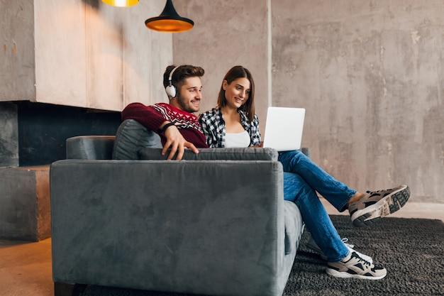 Giovani abbastanza felici sorridenti uomo e donna seduti a casa in inverno, guardando nel laptop, ascoltando le cuffie, studenti che studiano online, coppia nel tempo libero insieme, Foto Gratuite