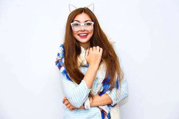 若い魅力的な流行に敏感な女性が白い壁にポーズ、楽しい笑顔、長い髪の明るいメイク、大きな居心地の良いスカーフ、面白いパーティー猫耳。明るい色、喜び、前向き、冬の時間。 無料写真