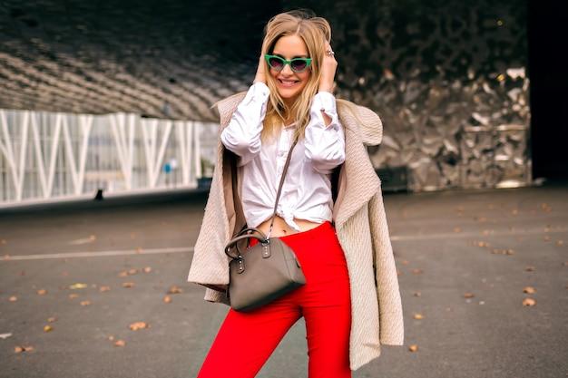 Молодая симпатичная хипстерская женщина позирует на улице возле современных бизнес-центров, в модном офисном наряде и кашемировом пальто, посылает поцелуй и наслаждается прохладным осенним днем в тонированных тонах. Бесплатные Фотографии