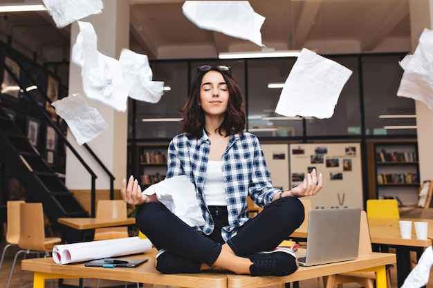테이블 서라운드 작업 물건과 비행 서류에 명상 젊은 꽤 즐거운 갈색 머리 여자. 쾌활한 분위기, 휴식, 일, 공부, 휴식, 진정한 감정. 무료 사진