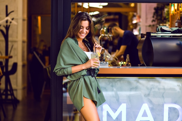 Young pretty lady enjoying free time at city cafeteria and bar, drinking lemon and having fun, trendy hipster outfit, toned colors. Free Photo
