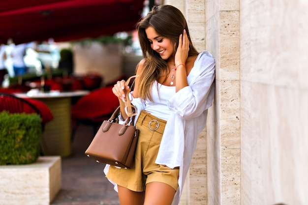 Young pretty magnificent shy brunette young woman posing on paris street, elegant lady look, summertime, beige colors, travel experience. Free Photo