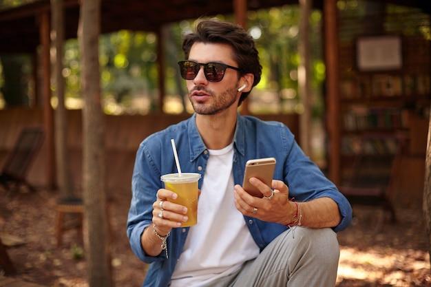 髭を生やした若いきれいな男性が不在になり、アイスティーを片手に街の庭でポーズをとり、携帯電話で電話をかけます 無料写真