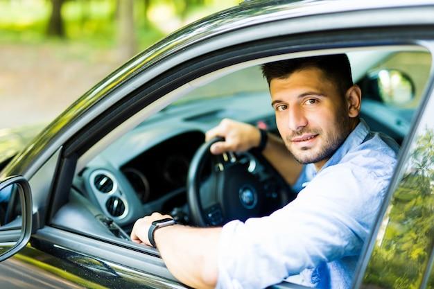 車に座っている若いきれいな男 Premium写真
