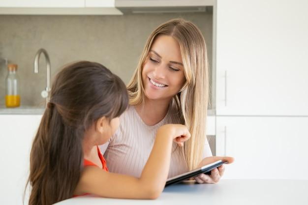 若い可愛いお母さんと娘のタブレットを使用して、お互いに笑顔します。 無料写真