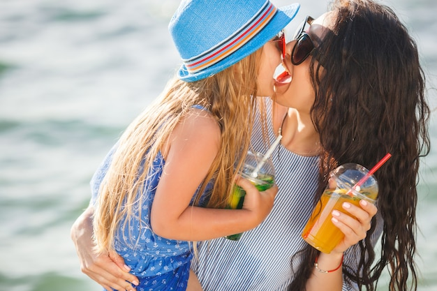 Young pretty mother and her little daughter on the beach having fun. girls drinking lemonade. Premium Photo