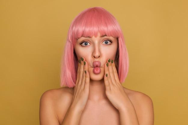 ピンクのボブの髪型で若いかなり開いた目の女性は彼女の頬に手を上げて、マスタードの壁の上に立っている間顔を作る 無料写真
