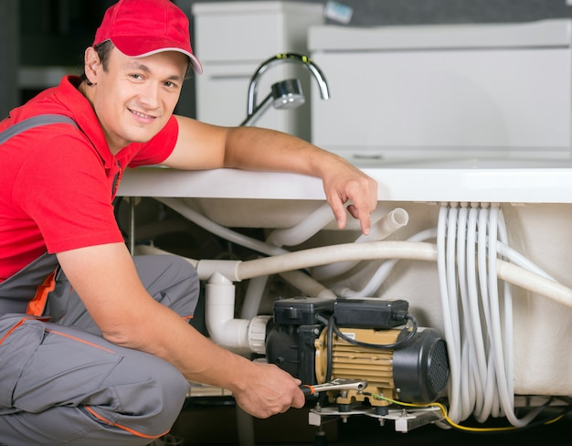 Young pretty plumber at work. Premium Photo