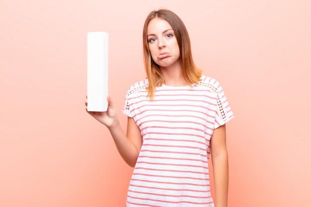悲しい、落ち込んで、不幸な若いかなり赤い頭の女性が単語や文を形成するアルファベットのiの文字を保持しています。 Premium写真