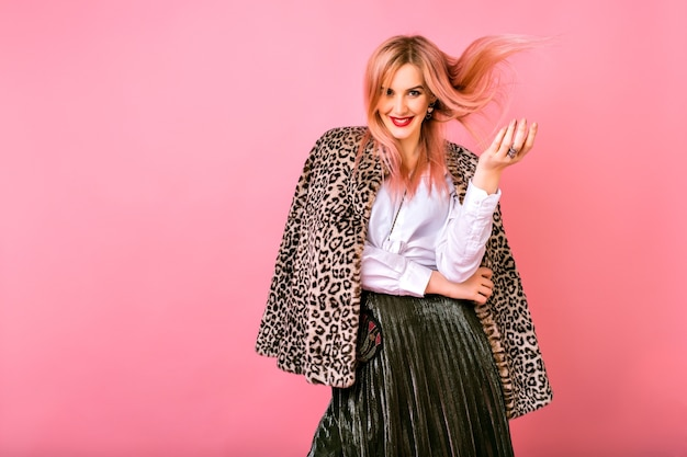 Young pretty sexy magnificent woman playing with her hairs, wearing evening sparkling cocktail outfit and fur leopard printed trendy coat, pink background, positive emotions. Free Photo