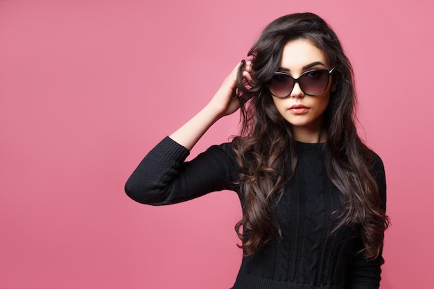 Young pretty sexy woman or girl with cute face and long brunette hair wearing sunglasses and black sweater, posing on pink background Premium Photo