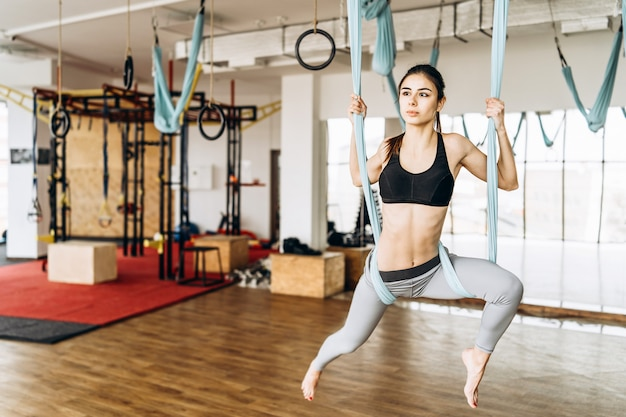 Young pretty slim body fitness girl practicing fly yoga in the gym. Premium Photo